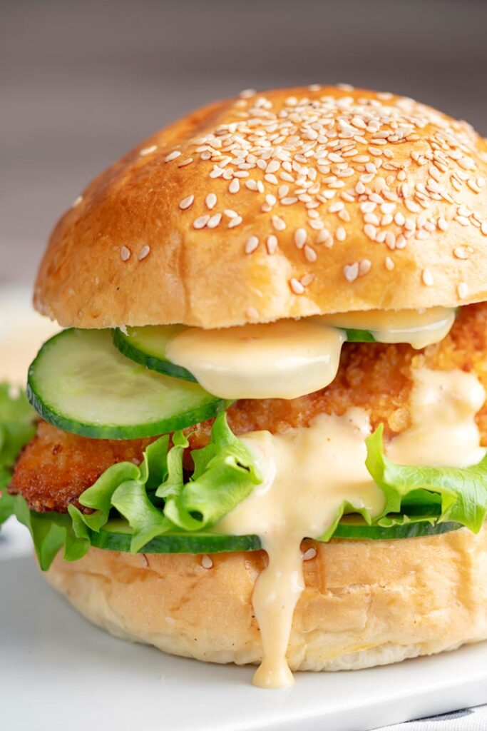 Portrait image of a chicken breast burger with lettuce and cucumber and a dollop of chilli and lime mayo