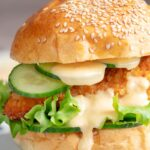 Portrait image of a chicken breast burger with lettuce and cucumber and a dollop of chilli and lime mayo with text overlay