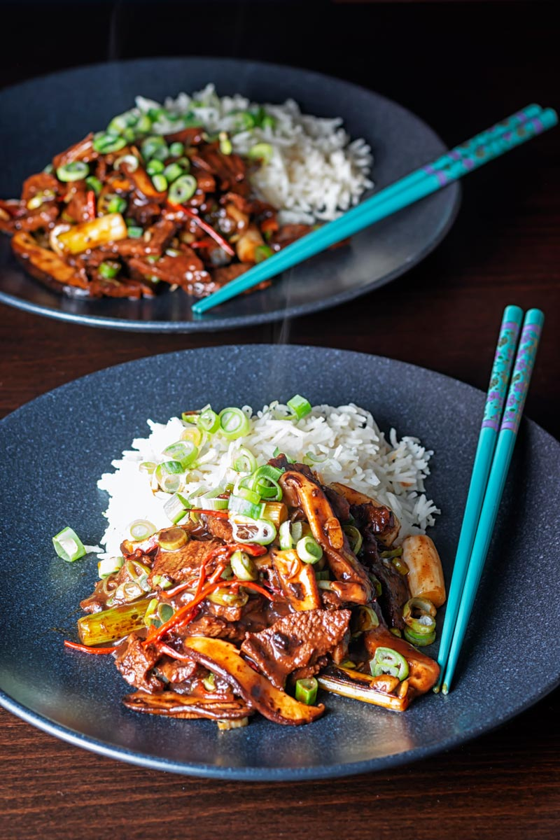 Portrait image of a streaming hot Chinese beef and shiitake mushroom stir fry served on two black plates
