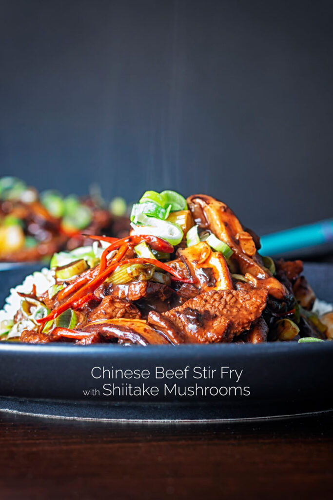 Portrait image of a streaming hot Chinese beef and shiitake mushroom stir fry served on a dark plate with text overlay
