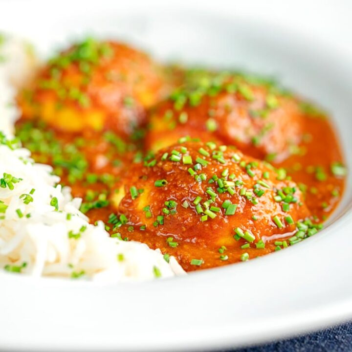 Square image of a hard boiled egg curry in a white bowl served with white rice and snipped chives