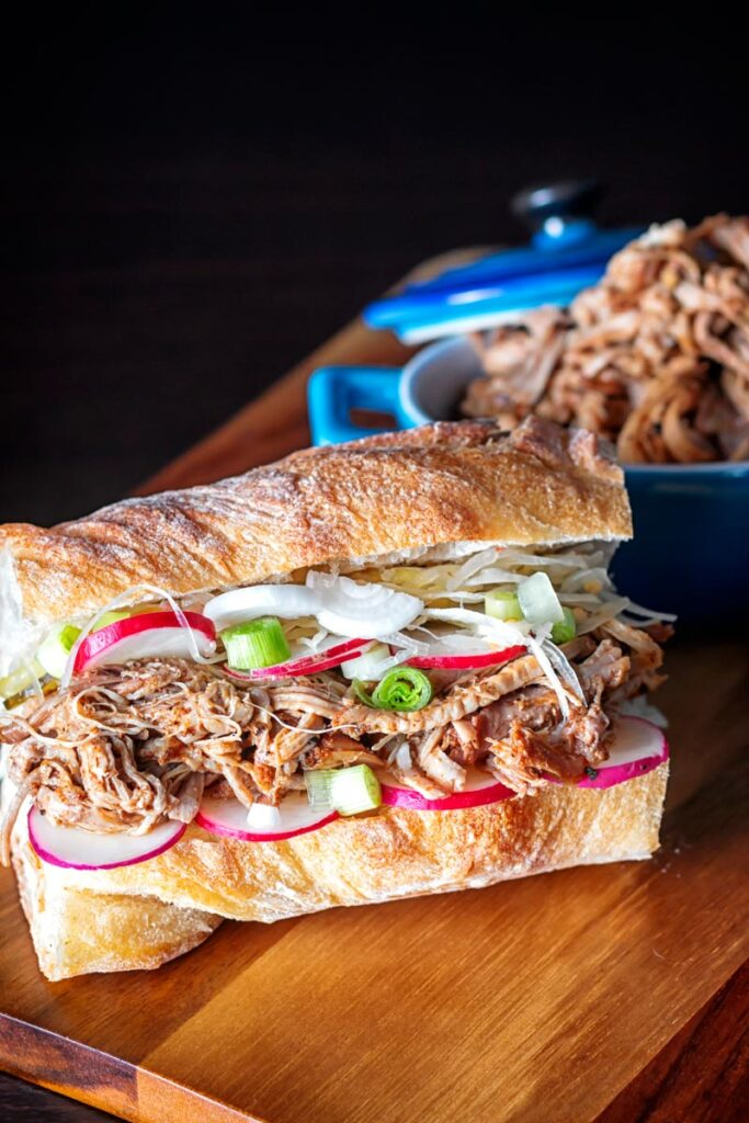 Portrait up image of a slow cooker pulled pork sandwich on a ciabatta style loaf with pickles