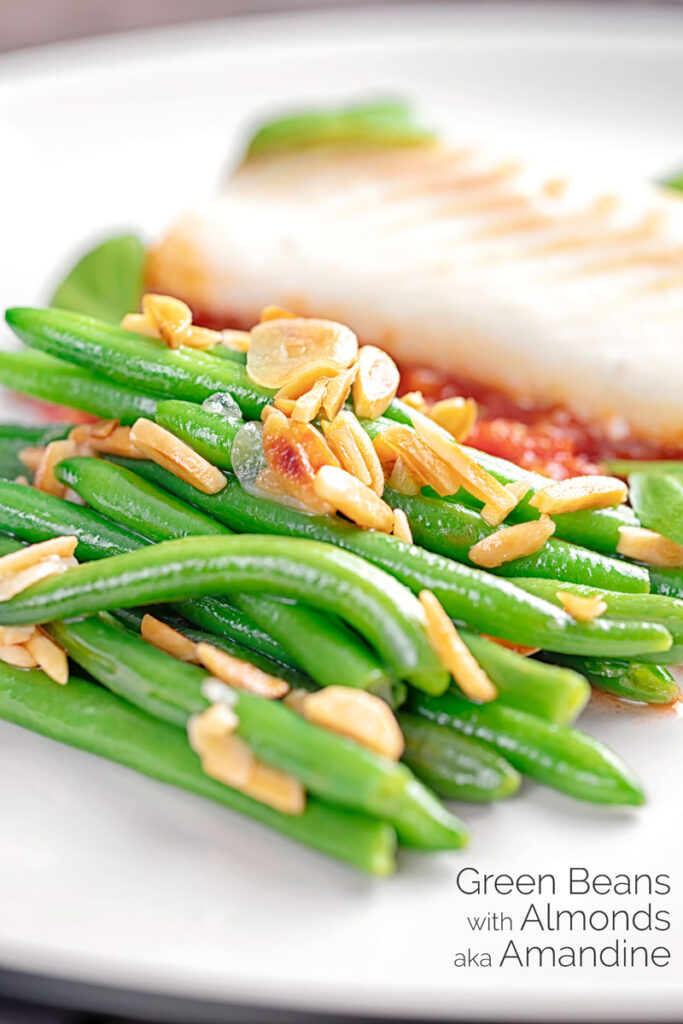 Portrait image of sauteed green beans garnished with toasted almonds served on a white place with fish in a tomato sauce with text overlay