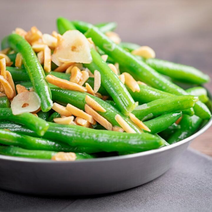 Square image of sauteed green beans garnished with toasted almonds