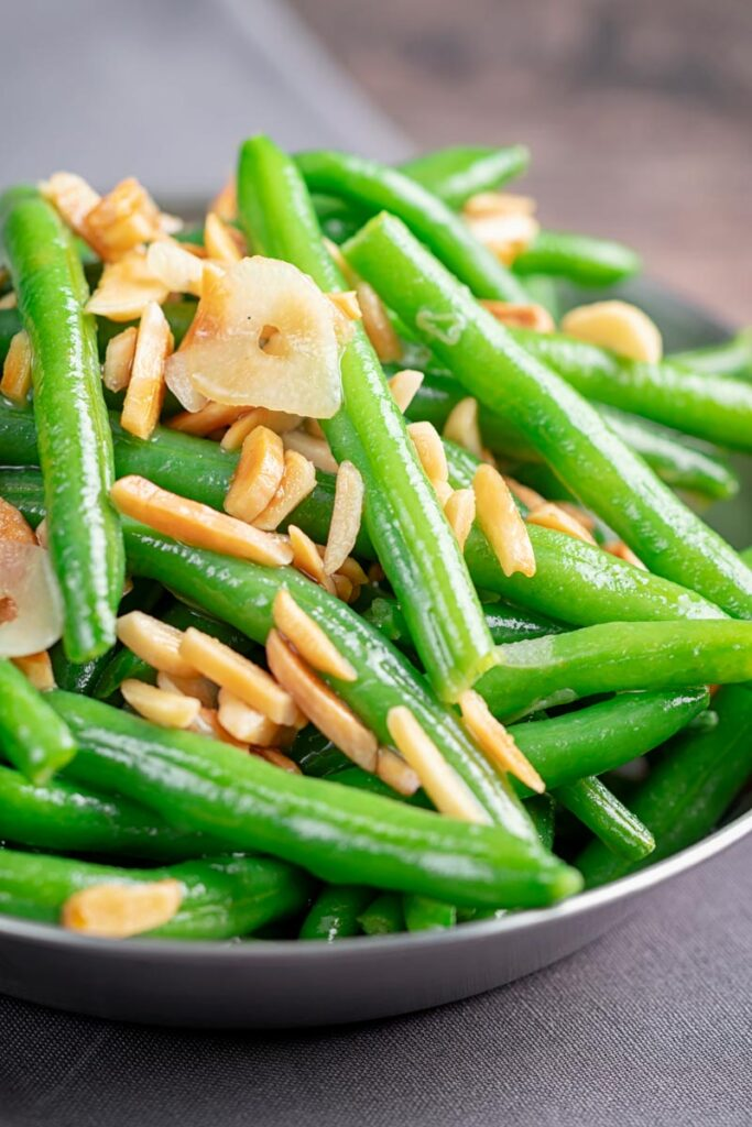Portrait image of sauteed green beans garnished with toasted almonds