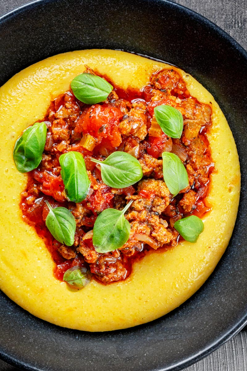 Portrait overhead image of an Italian sausage ragu served on cheesy polenta with fresh basil leaves in a black bowl