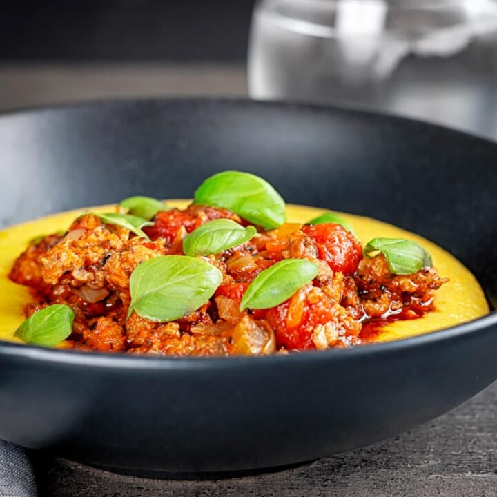 Square image of an Italian sausage ragu served on cheesy polenta with fresh basil leaves in a black bowl