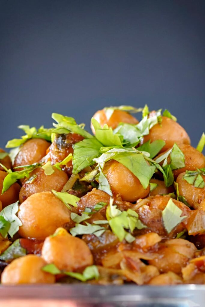 Portrait close up image of a chole or Indian chickpea curry garnished with chopped coriander