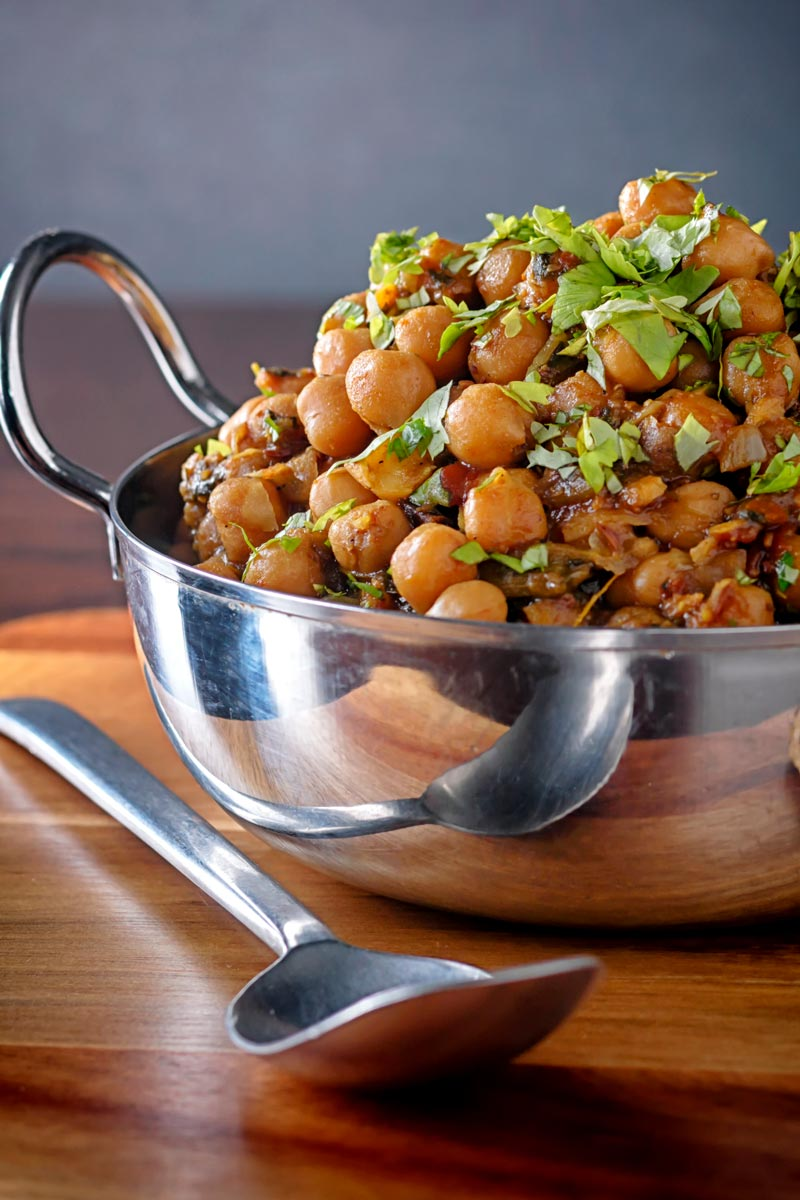 Portrait image of a chole or Indian chickpea curry garnished with chopped coriander served in a karahi
