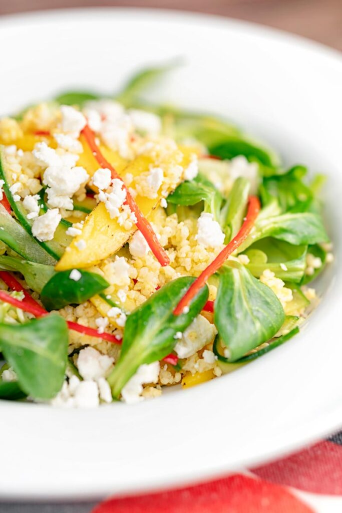 Portrait image of a main course mango salad featuring lambs lettuce with feta cheese, millet and chilli shreds