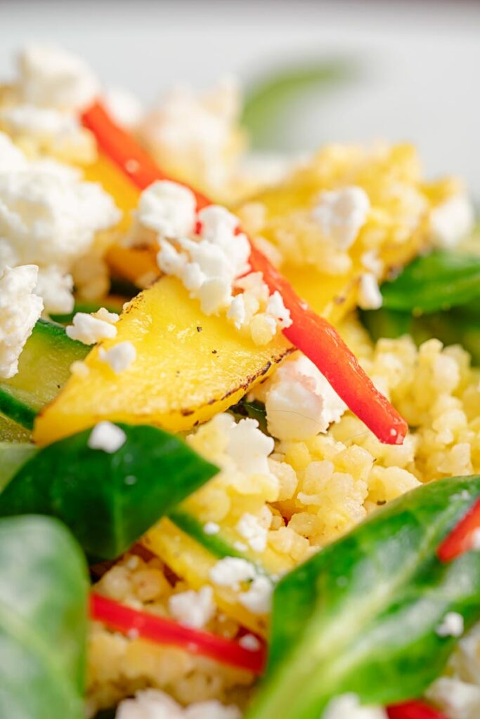 Portrait close up image of a main course mango salad featuring lambs lettuce with feta cheese, millet and chilli shreds