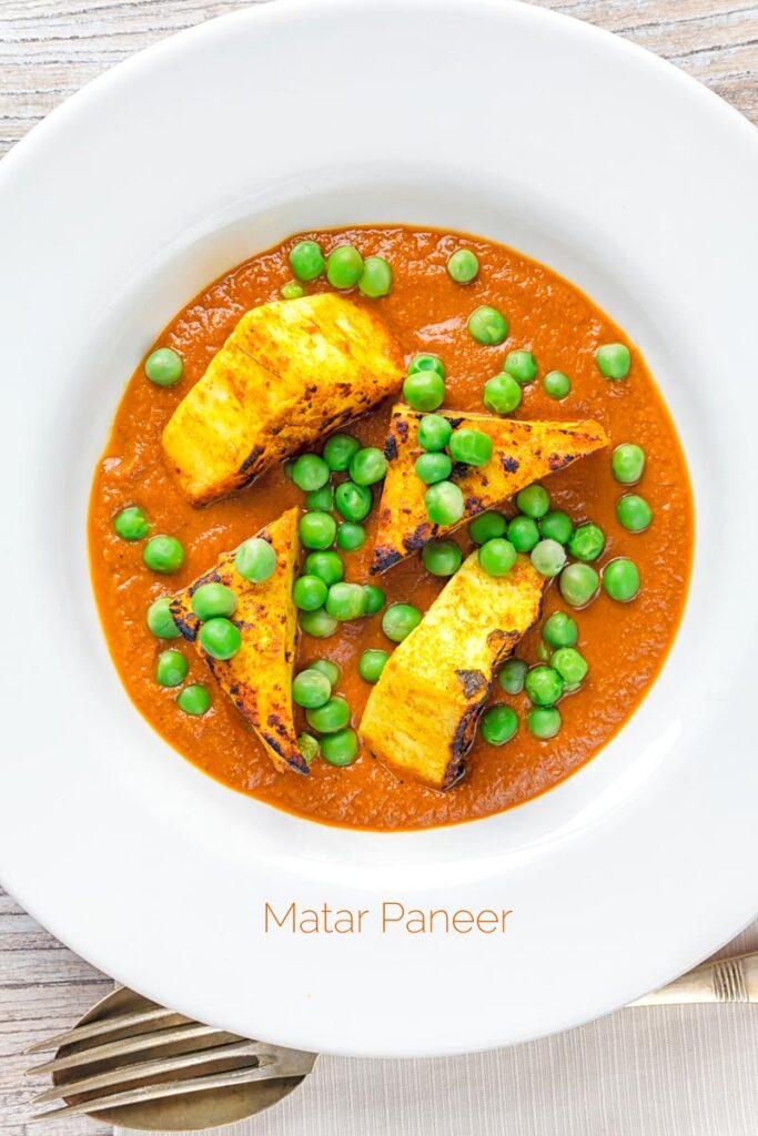 Portrait overhead image of a matar paneer curry in a masala sauce served in a white bowl with text overlay