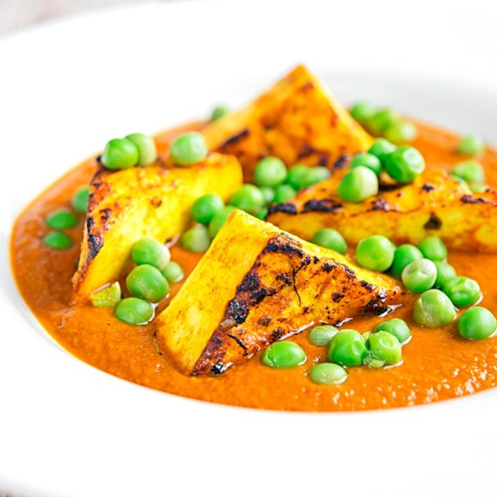 Square image of a matar paneer curry in a masala sauce served in a white bowl