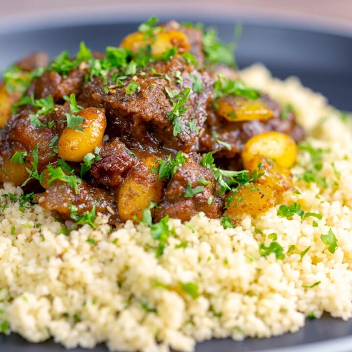 Square image of a rich Moroccan Lamb tagine with almonds in a date sauce served on buttered couscous