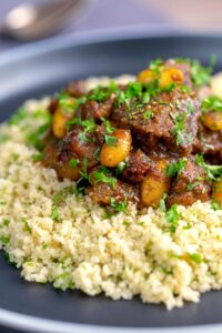 Portrait image of a rich Moroccan Lamb tagine with almonds in a date sauce served on buttered couscous
