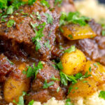 Portrait close up image of a rich Moroccan Lamb tagine with almonds in a date sauce served on buttered couscous with text overlay