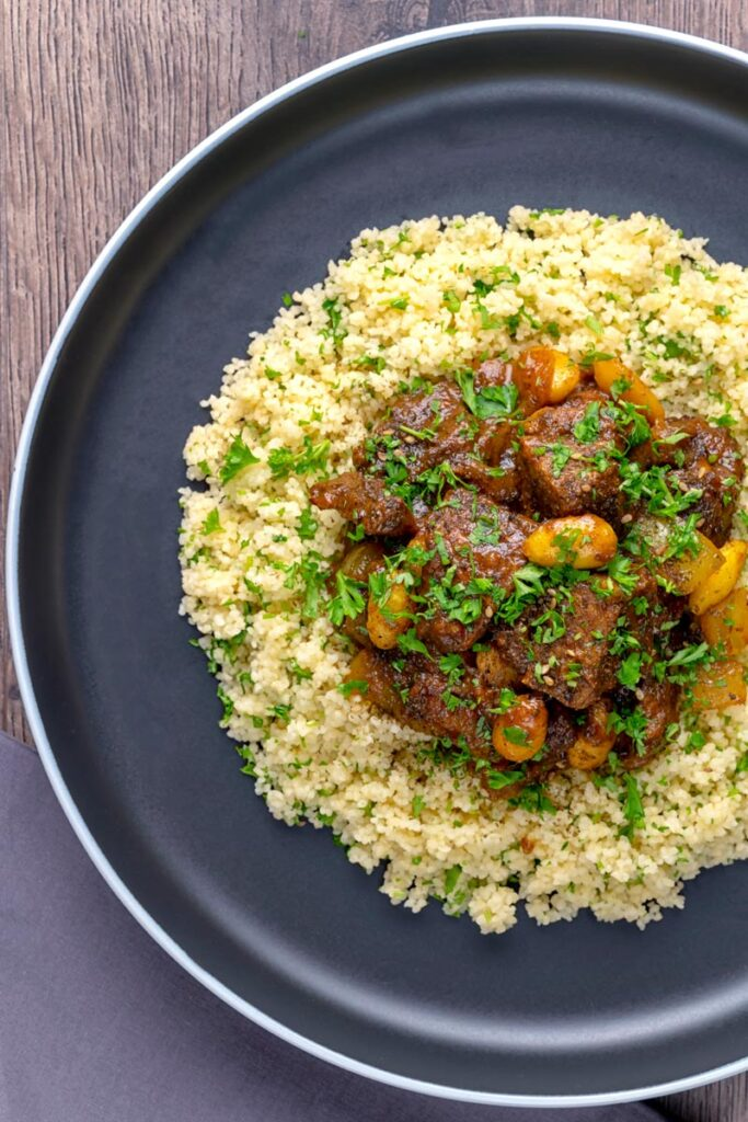 Portrait overhead image of a rich Moroccan Lamb stew with almonds in a date sauce served on buttered couscous