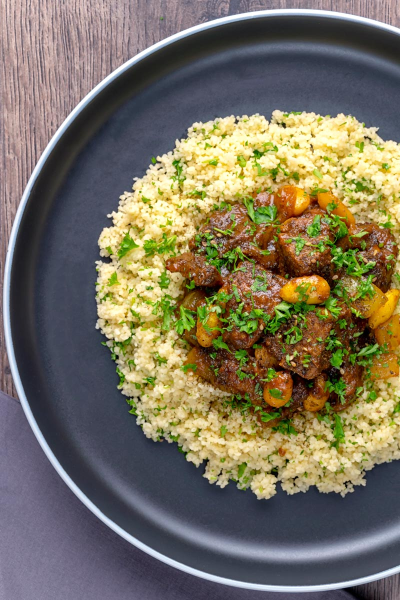 Portrait overhead image of a rich Moroccan Lamb tagine with almonds in a date sauce served on buttered couscous