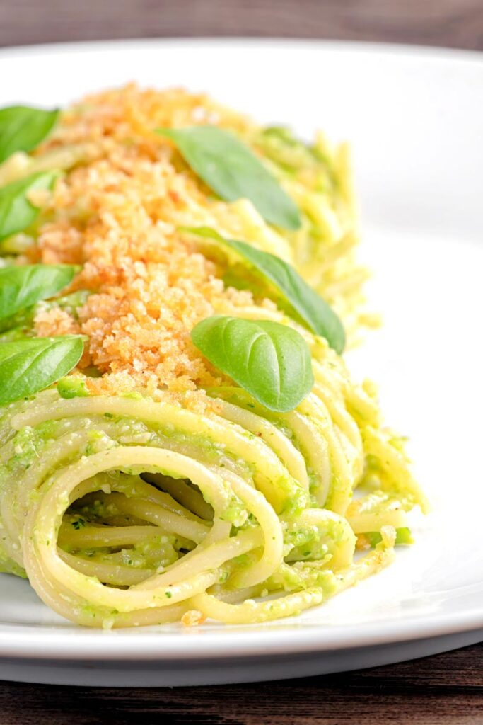Portrait image of pea pesto pasta with toasted bread crumbs and fresh basil leaves elegantly presented on a white plate