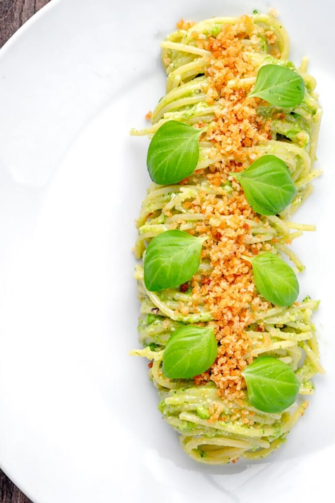 Portrait overhead image of pea pesto pasta with toasted bread crumbs and fresh basil leaves elegantly presented on a white plate