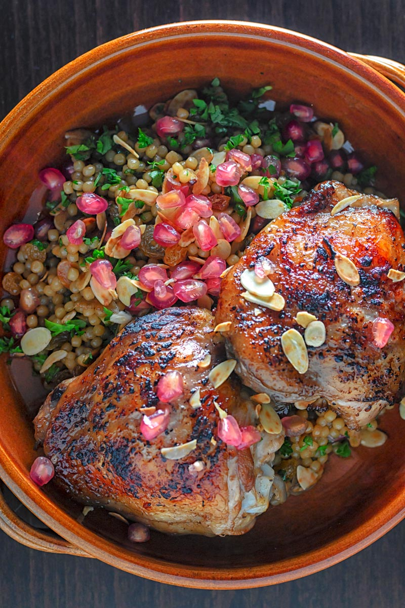 Portrait overhead image of pomegranate molasses glazed chicken thighs served with Israeli couscous and pomegranate seeds
