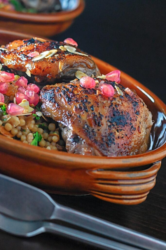 Portrait close up image of pomegranate molasses glazed chicken thighs served with Israeli couscous and pomegranate seeds
