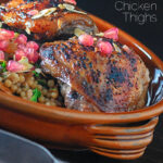Portrait close up image of pomegranate molasses glazed chicken thighs served with Israeli couscous and pomegranate seeds with text overlay
