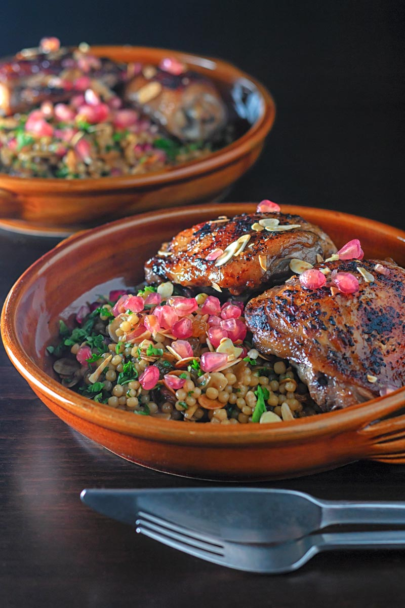Portrait image of pomegranate molasses glazed chicken thighs served with Israeli couscous and pomegranate seeds