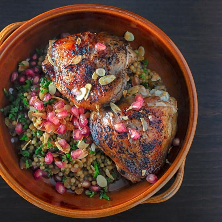 Square overhead image of pomegranate molasses glazed chicken thighs served with Israeli couscous and pomegranate seeds