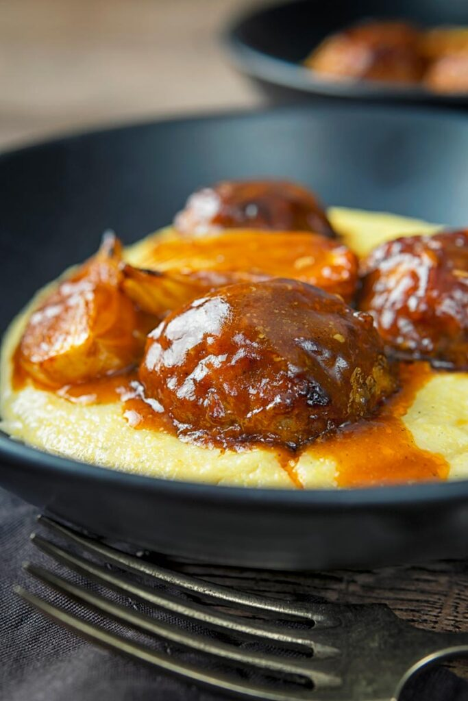 Portrait image of pork meatballs in bbq sauce served on polenta in a black bowl
