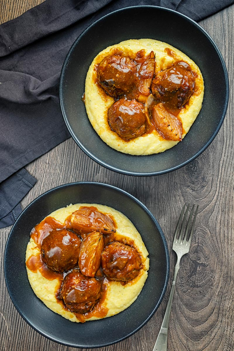 Portrait overhead image of pork meatballs in bbq sauce served on polenta in a black bowls