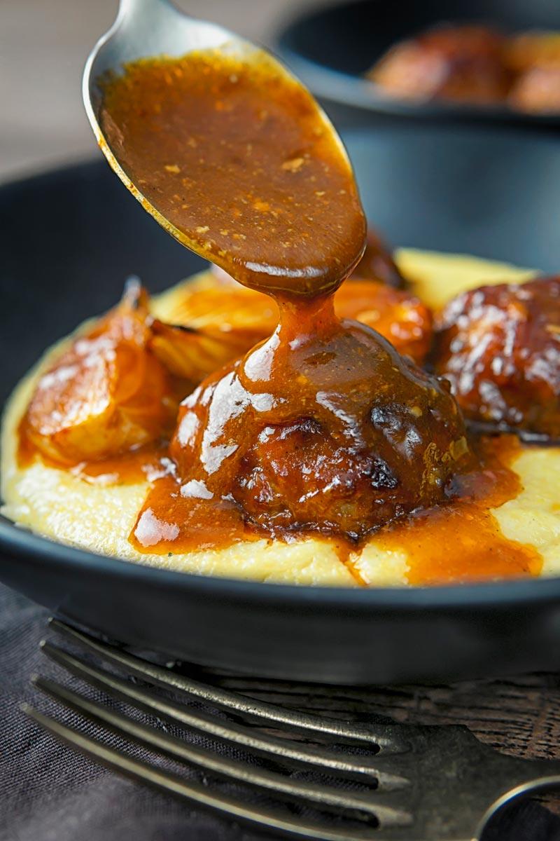Portrait image of BBQ sauce being poured over pork meatballs served in black plate on a polenta porridge