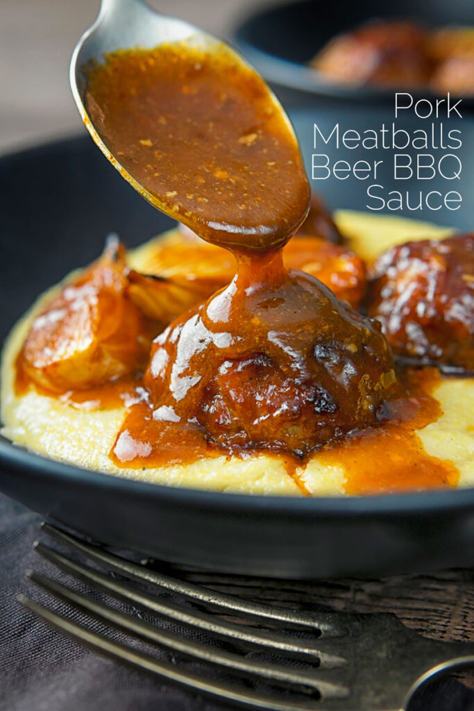Portrait image of BBQ sauce being poured over pork meatballs served in black plate on a polenta porridge with text overlay
