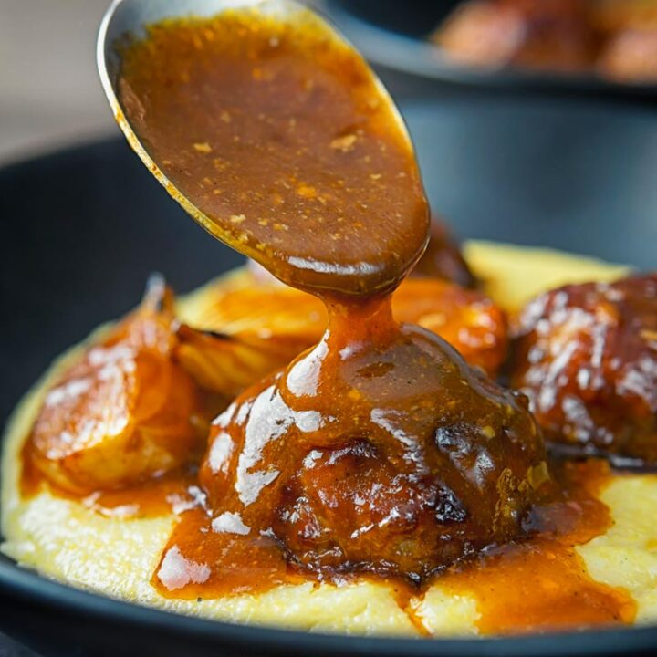 Square image of BBQ sauce being poured over pork meatballs served in black plate on a polenta porridge