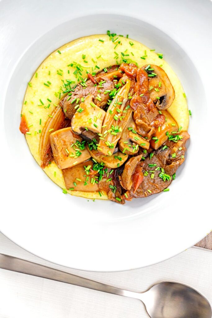Portrait overhead image of a mushroom ragu served on polenta porridge with shipped chives served in a white bowl