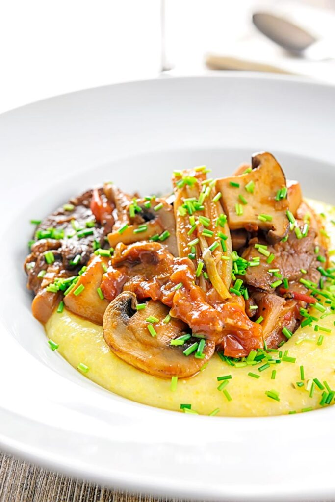 Portrait image of a mushroom ragu served on polenta porridge with shipped chives served in a white bowl