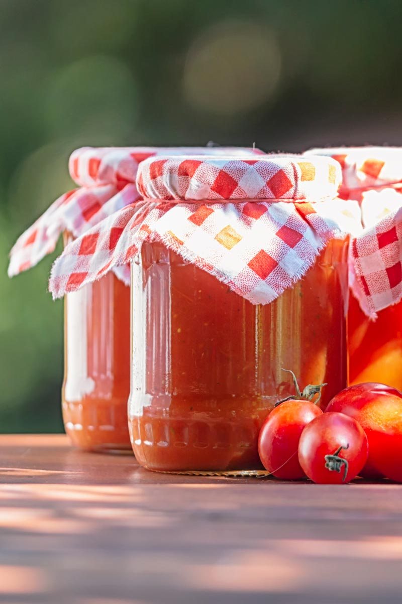 Portrait image of jars of roasted tomato passata with fresh tomatoes