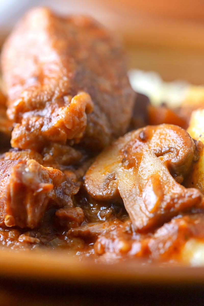 Portrait close up image of a tomato based wild boar stew with mushrooms