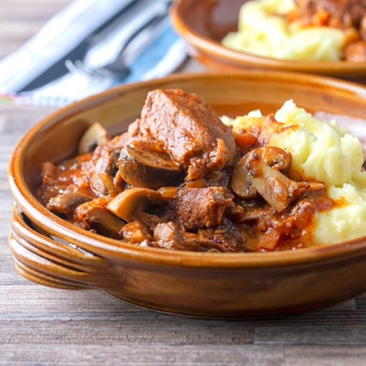 Square image of a tomato based wild boar stew with mushrooms served in a an earthenware bowl with mashed potatoes