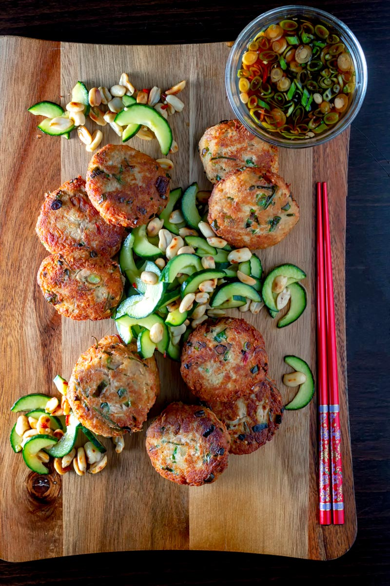 Portrait overhead image of spicy Thai tuna fish cakes served with a cucumber and peanut salad and a dipping sauce.