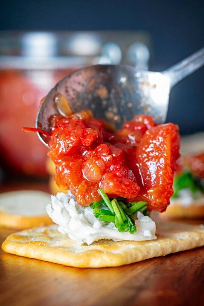 Portrait image of a tomato and chilli jam being spooned over cheese and crackers