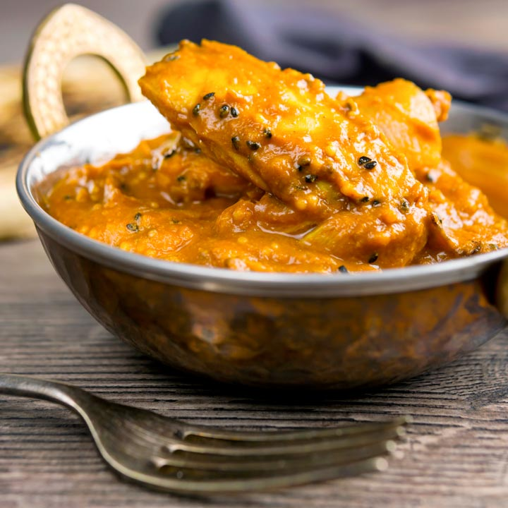 Square image of a chicken jalfrezi curry served in a tarnished copper covered karahi bowl