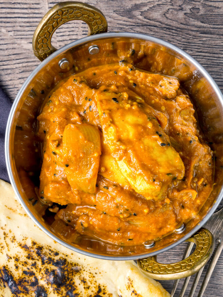 Portrait overhead image of a chicken jalfrezi curry served in a tarnished copper covered karahi bowl
