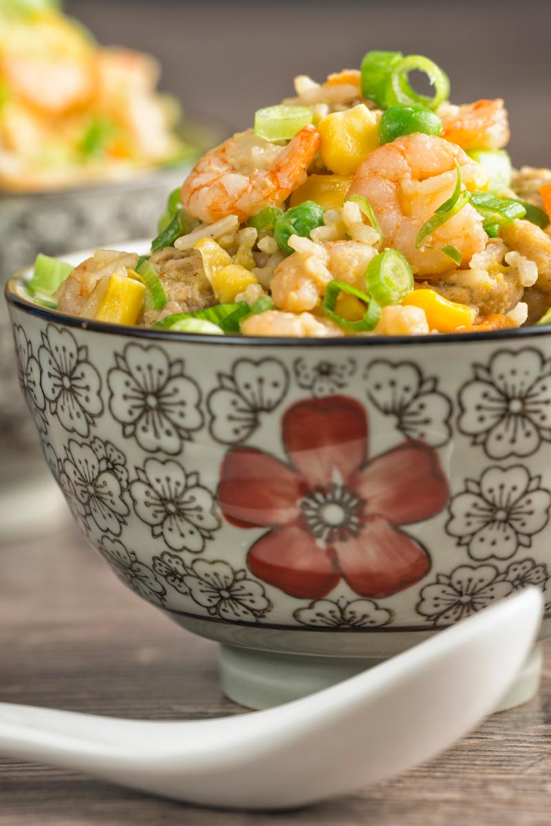 Portrait image of Chinese Fried rice served in bowls decorated with an Asian stylised design