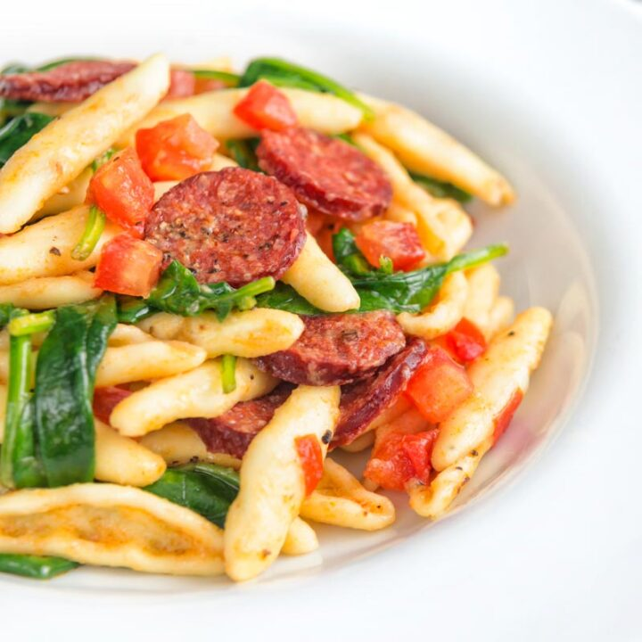 Square image of chorizo pasta served with wilted spinach and fresh tomato cubes