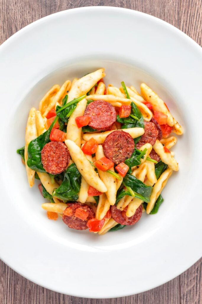 Portrait over head image of cured sausage pasta served with wilted spinach and fresh tomato cubes in a white bowl