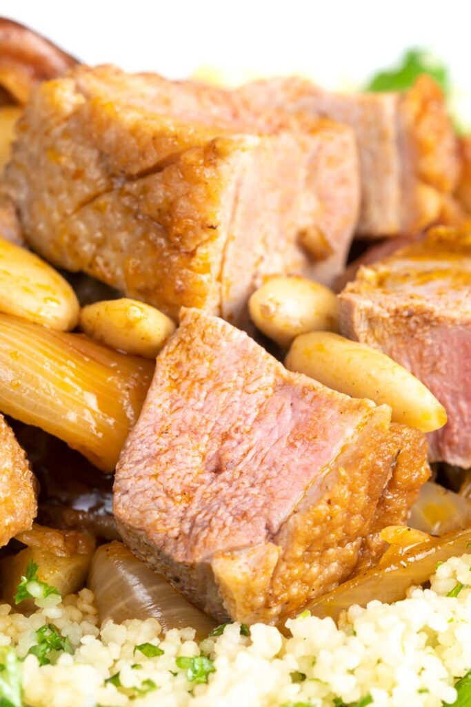 Portrait close up image of a light duck breast stew with North African flavours served with buttered couscous