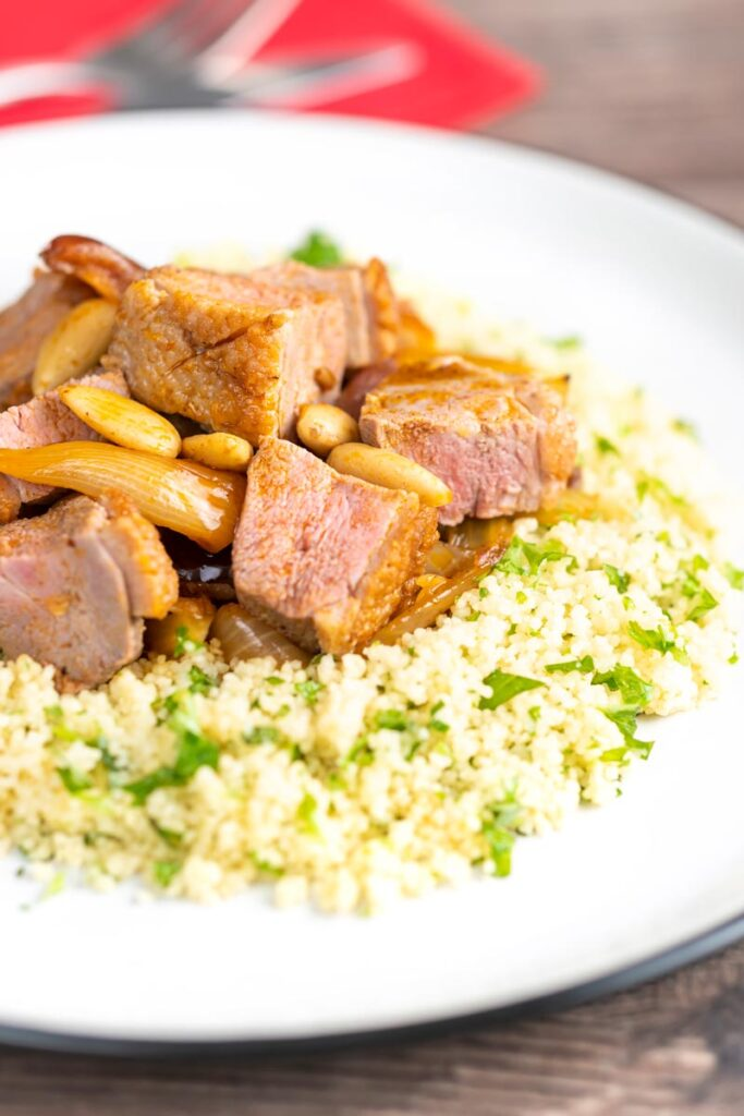Portrait image of a light duck breast tagine with North African flavours served with buttered couscous