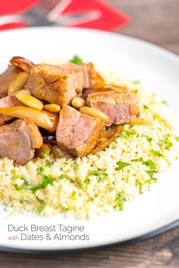 Portrait image of a lighter duck breast tagine served with buttered couscous, and featuring a text overlay.