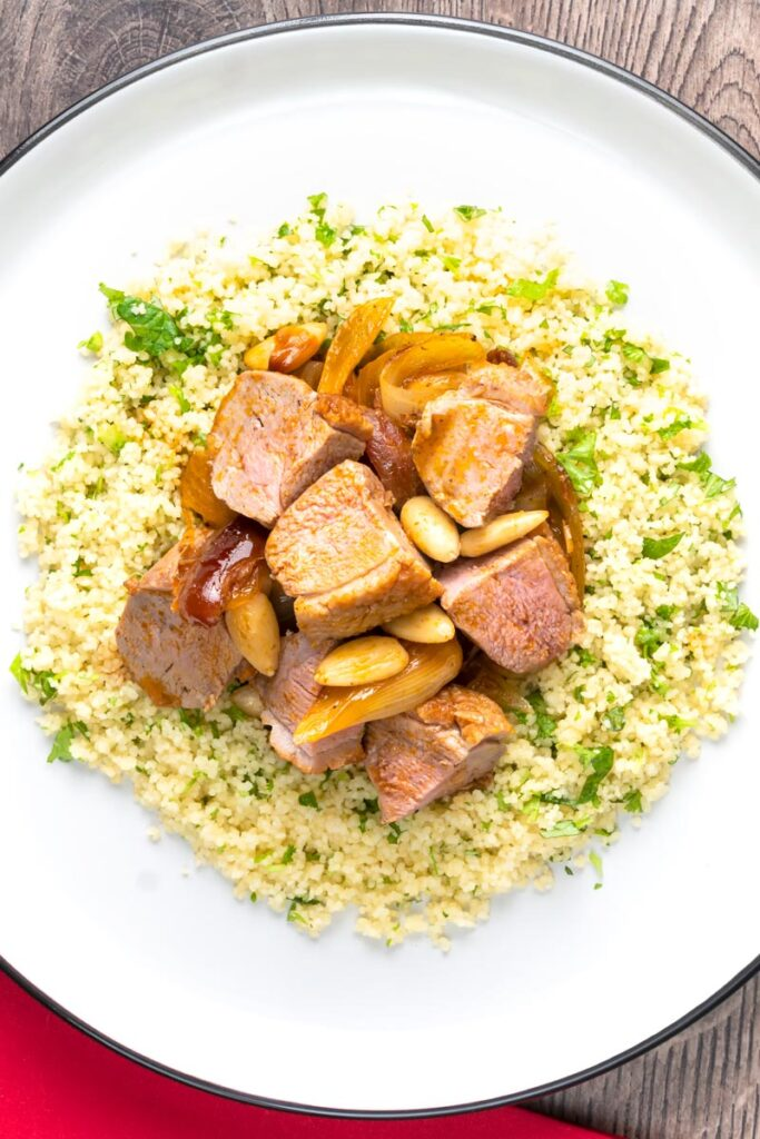 Portrait overhead image of a light duck breast stew with North African flavours served with buttered couscous